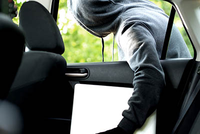 Thief stealing a laptop out of a open car window